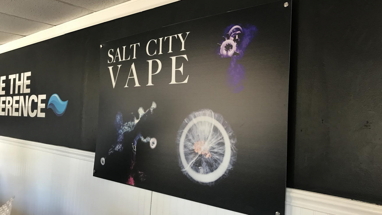 "Black Sign on a white and black wall, the words ""Salt City Vape"""