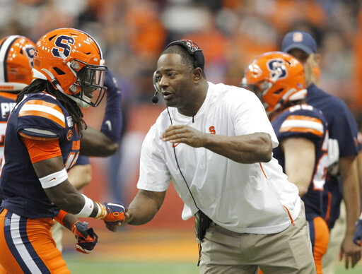 Syracuse head coach Dino Babers, right, greets players as they leave the field in the second half of an NCAA college football game against Pittsburgh in Syracuse, N.Y., Friday, Oct. 18, 2019. Pittsburgh won 27-20.