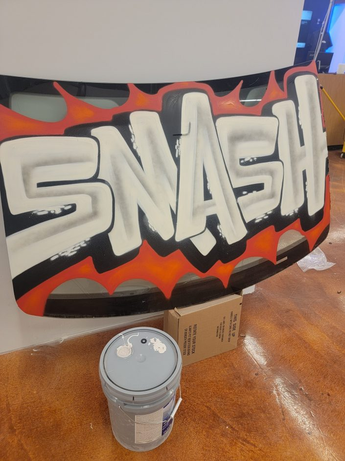 """Car windshield with the word """"smashed"""" graffiti across it."""