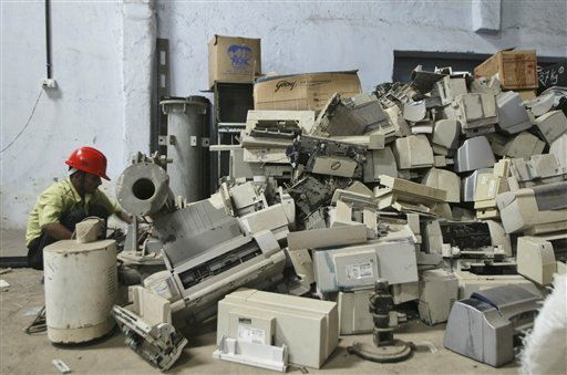 This photo shows a stack of old electronics like computers televisions etc. waiting to be recycled.