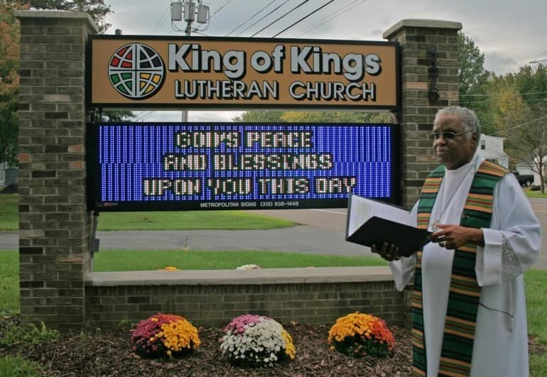 Reverend Julius Carroll speaks in front of a King of Kings Lutheran Church sign