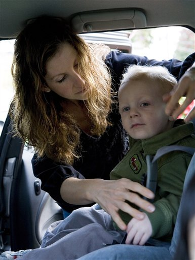 Child gets strapped in by a woman