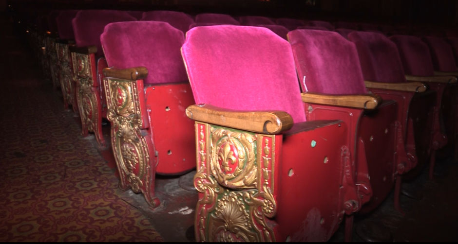 The seats at the Landmark Theatre have aged, pink covering and worn down metal and wood framing.