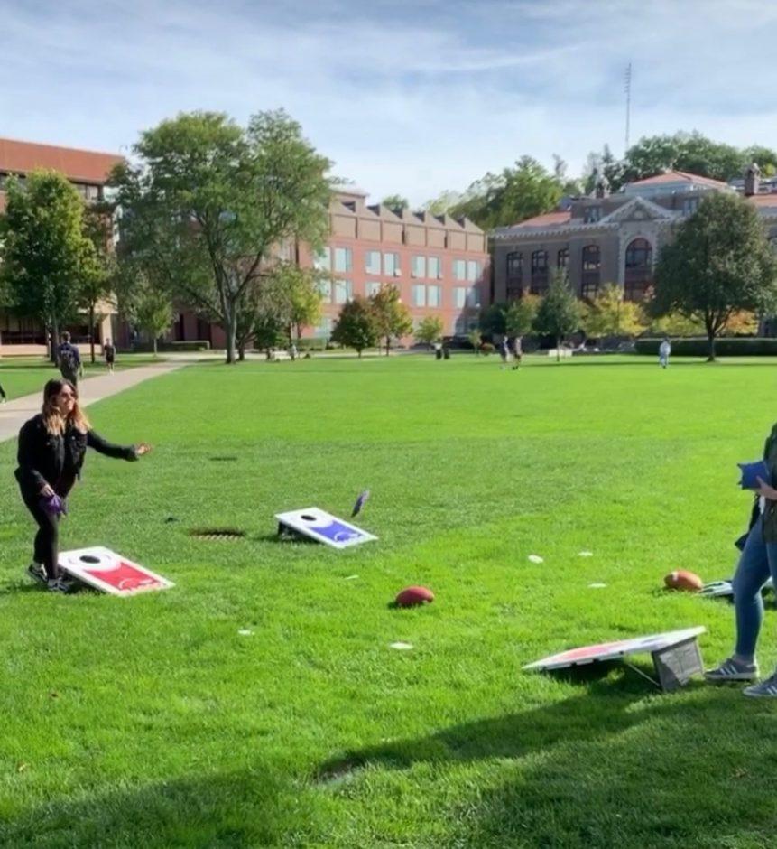 Two students playing cornhole.