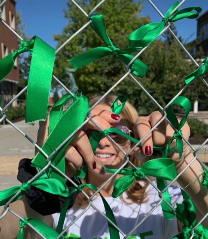 A student tying a ribbon on a fence.