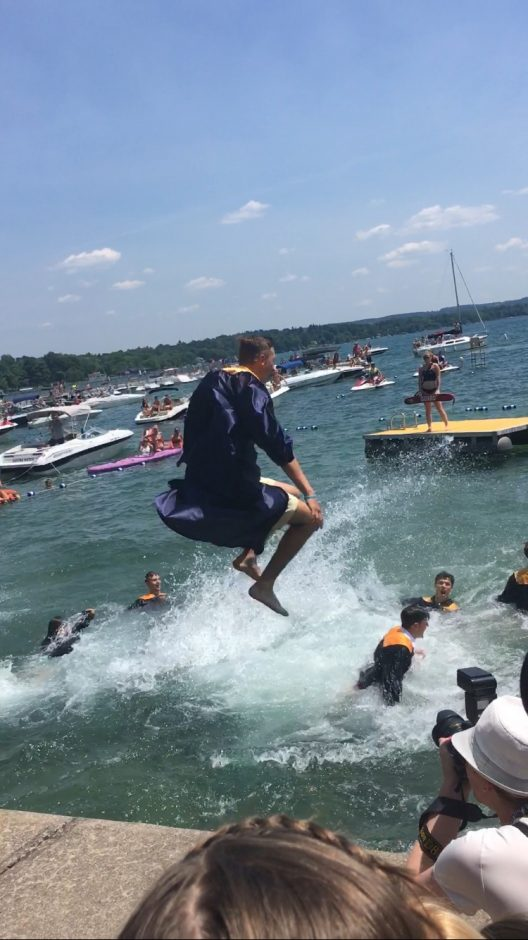 Jacob Patalino jumps into Skaneateles Lake in his graduation gown
