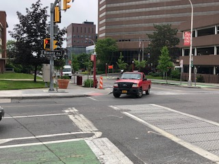 a red truck, making a turn on Waverly and University Intersection.