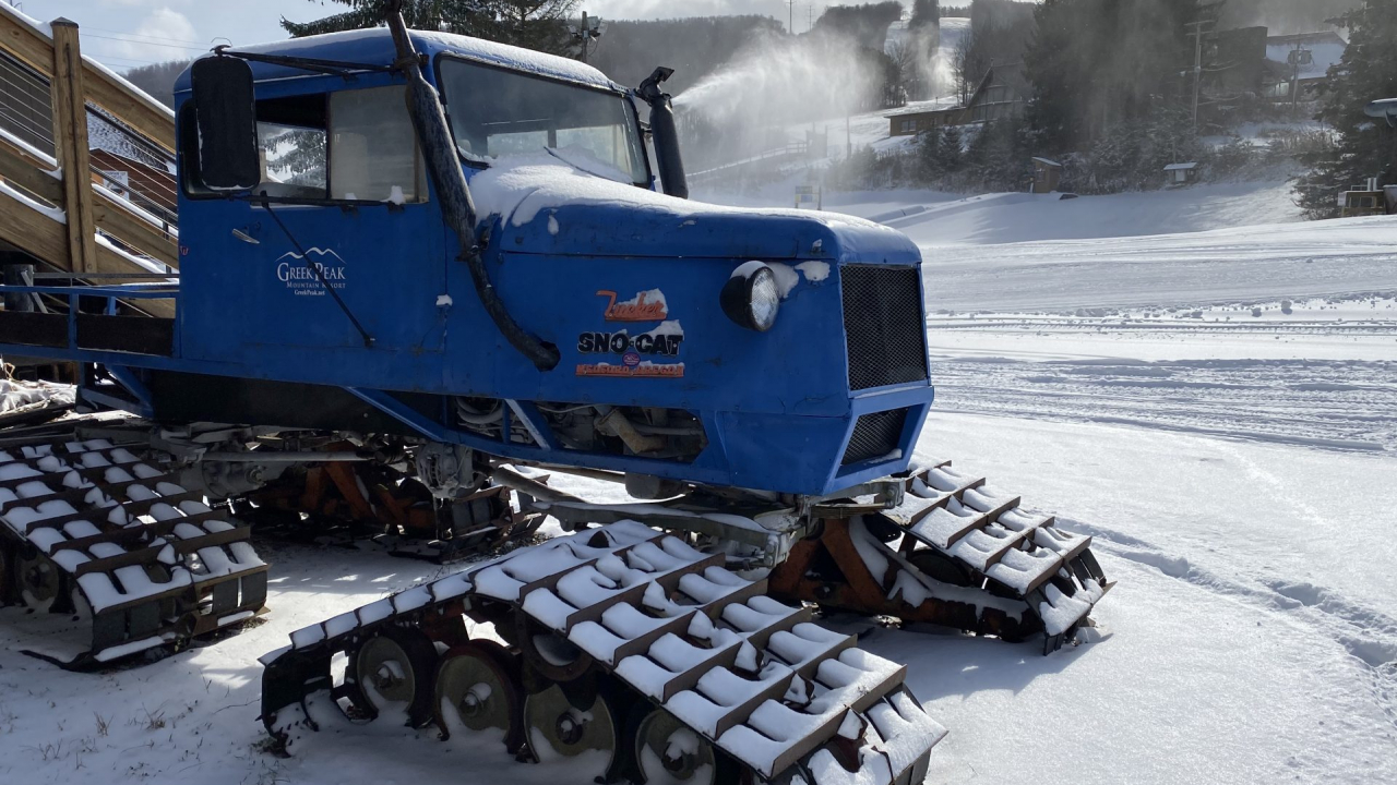 Snow groomer in front of face of Greek Peak Mountain Resort