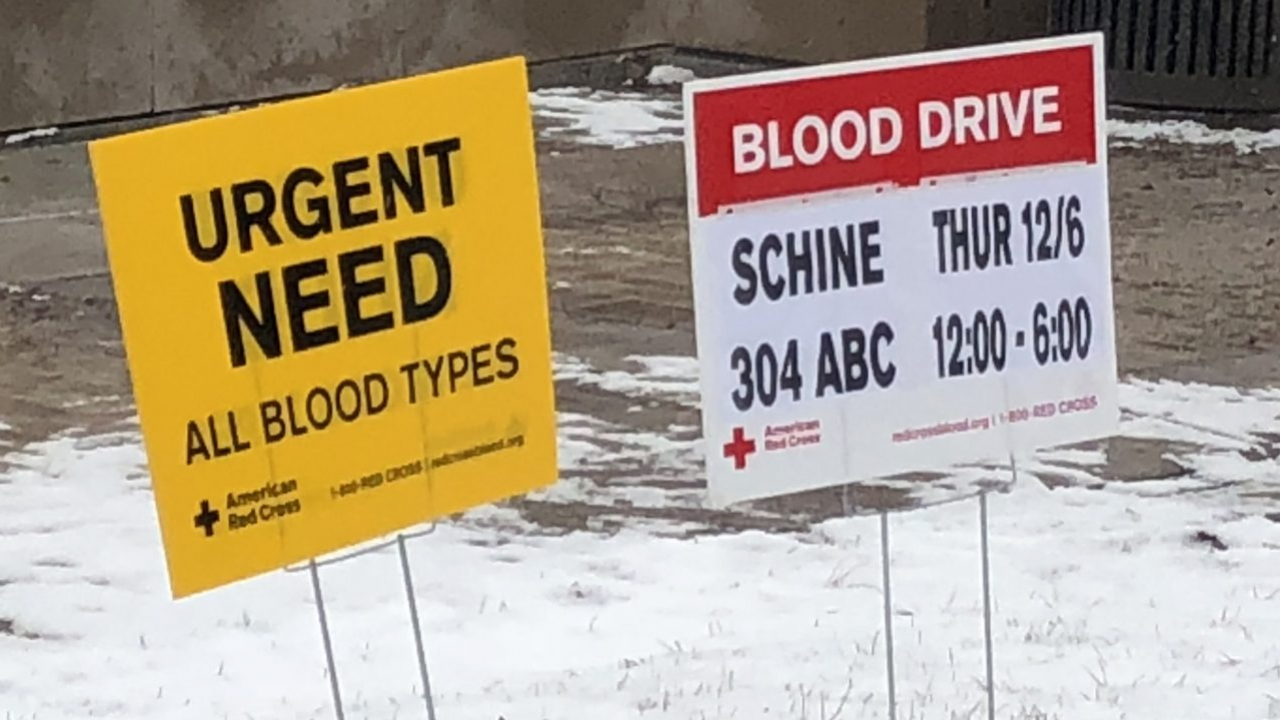 Two signs promoting the blood drive are popped up in some snow