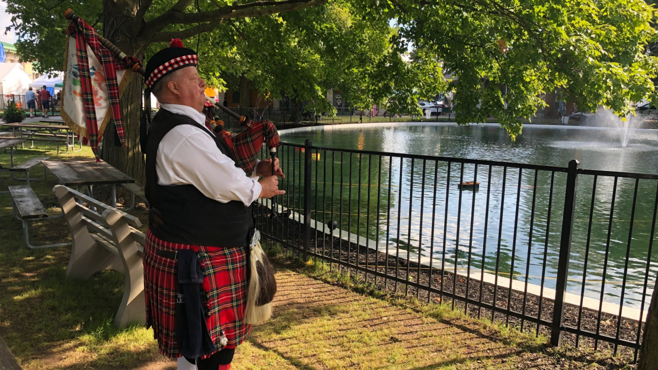 Jack Hines rehearses on his bagpipes by the pond at the NY State Fair.