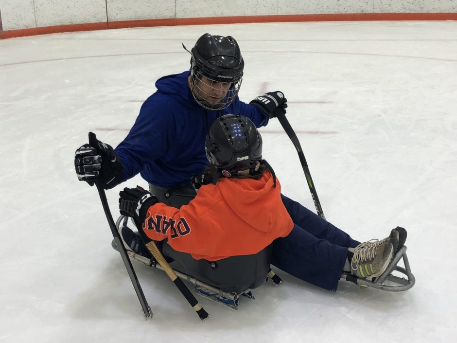 A father and his son in sleds on ice