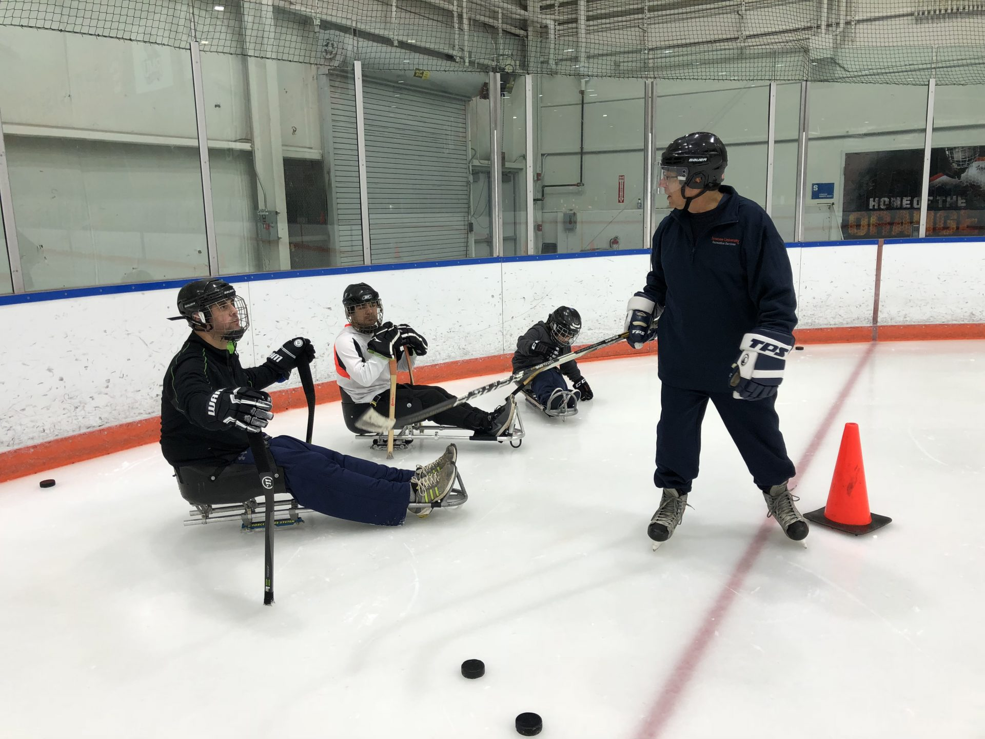 3 players in sleds on the ice. A coach giving players directions