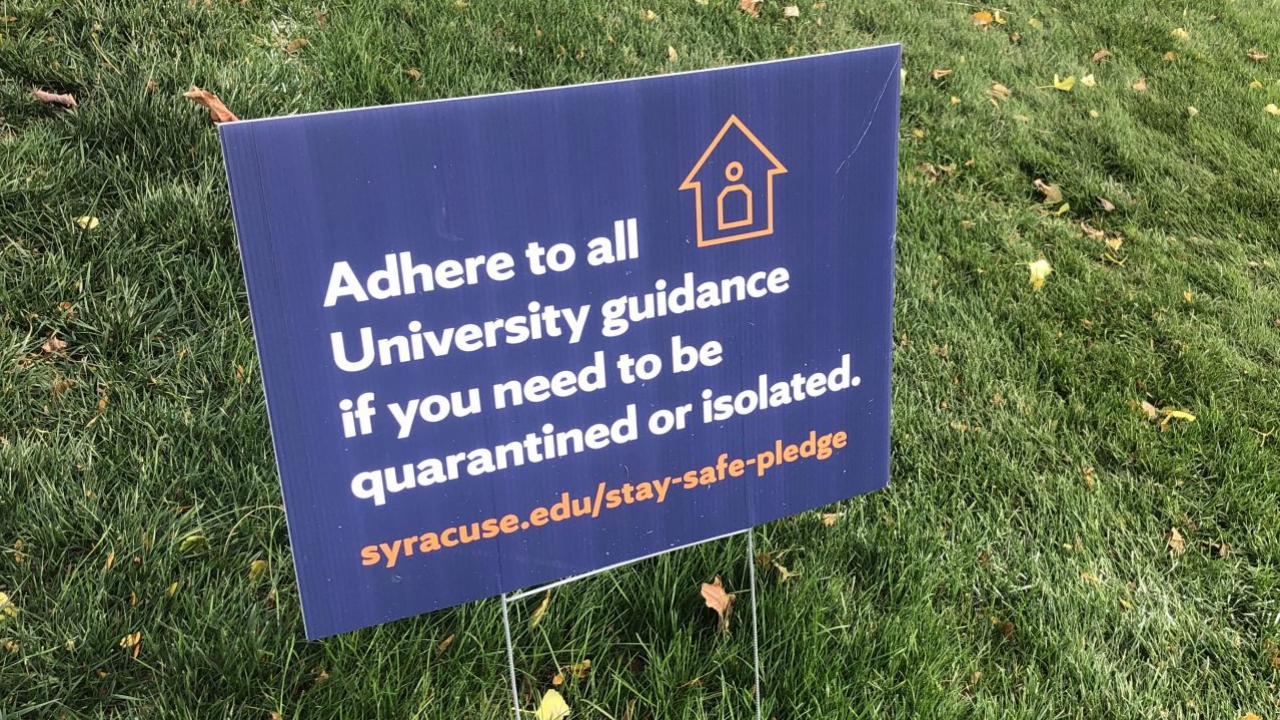 A sign on the campus of Syracuse University advising people to follow Syracuse University guidance if someone needs to enter quarantine or a period of isolation.