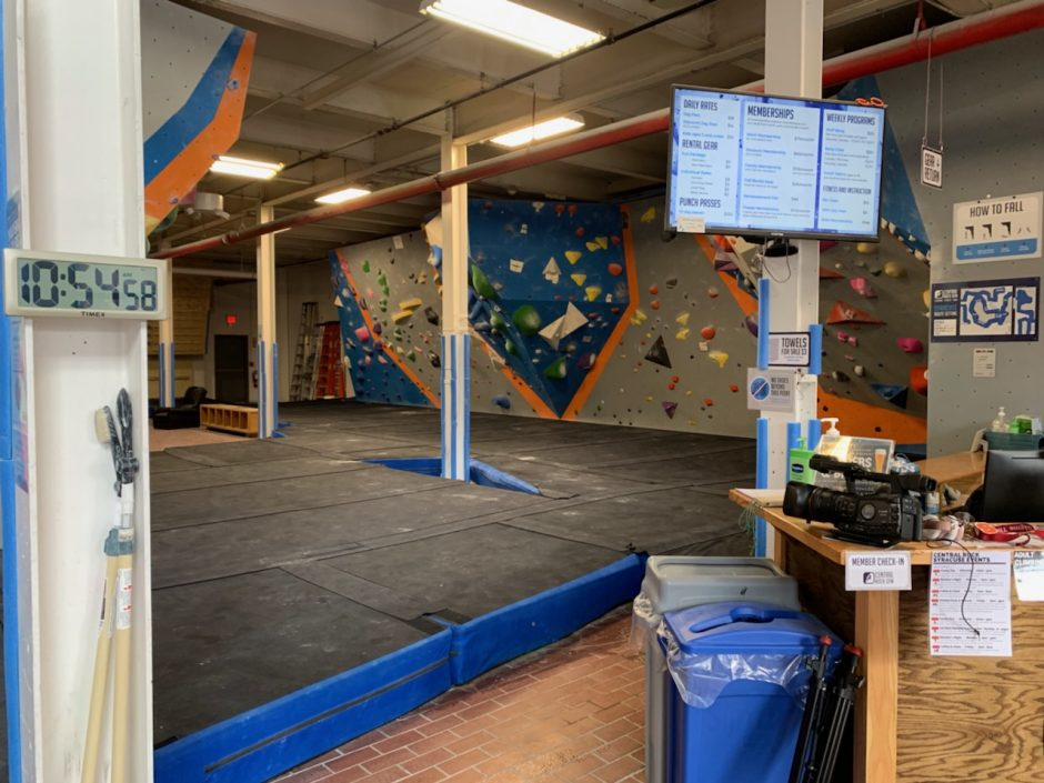 wide shot of rock climbing gym black floors gray walls