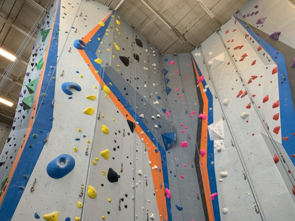 tall rock climbing wall with gray blue and orange stripes