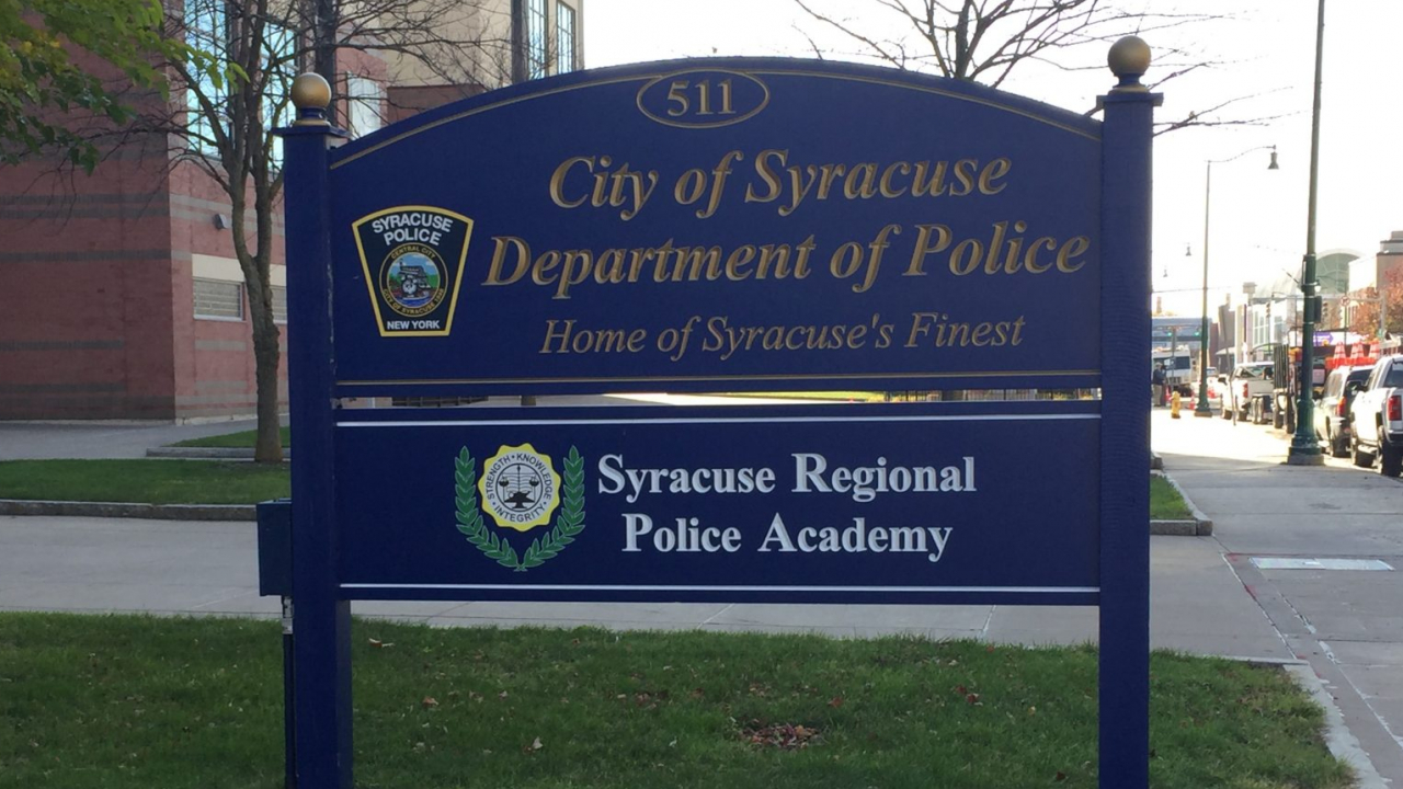 """A blue sign that reads """"City of Syracuse Department of Police: Home to Syracuse's Finest."""""""