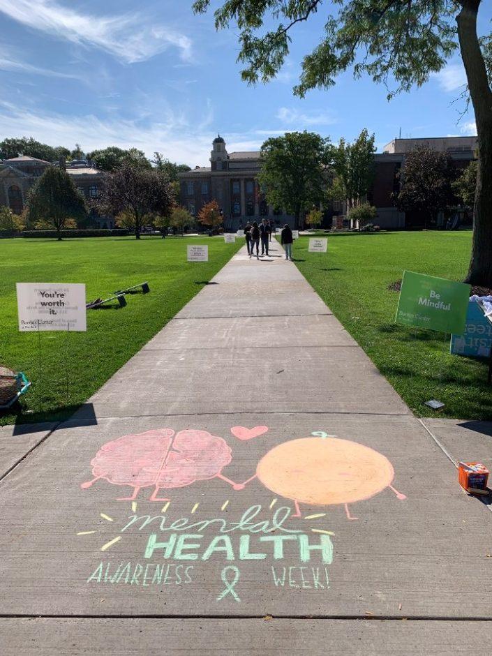 Mental Health Awareness message written in chalk on the quad sidewalks.