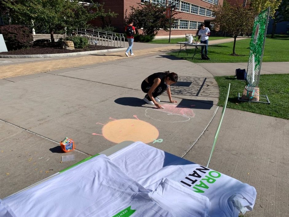 A student using chalk to write on the sidewalk.