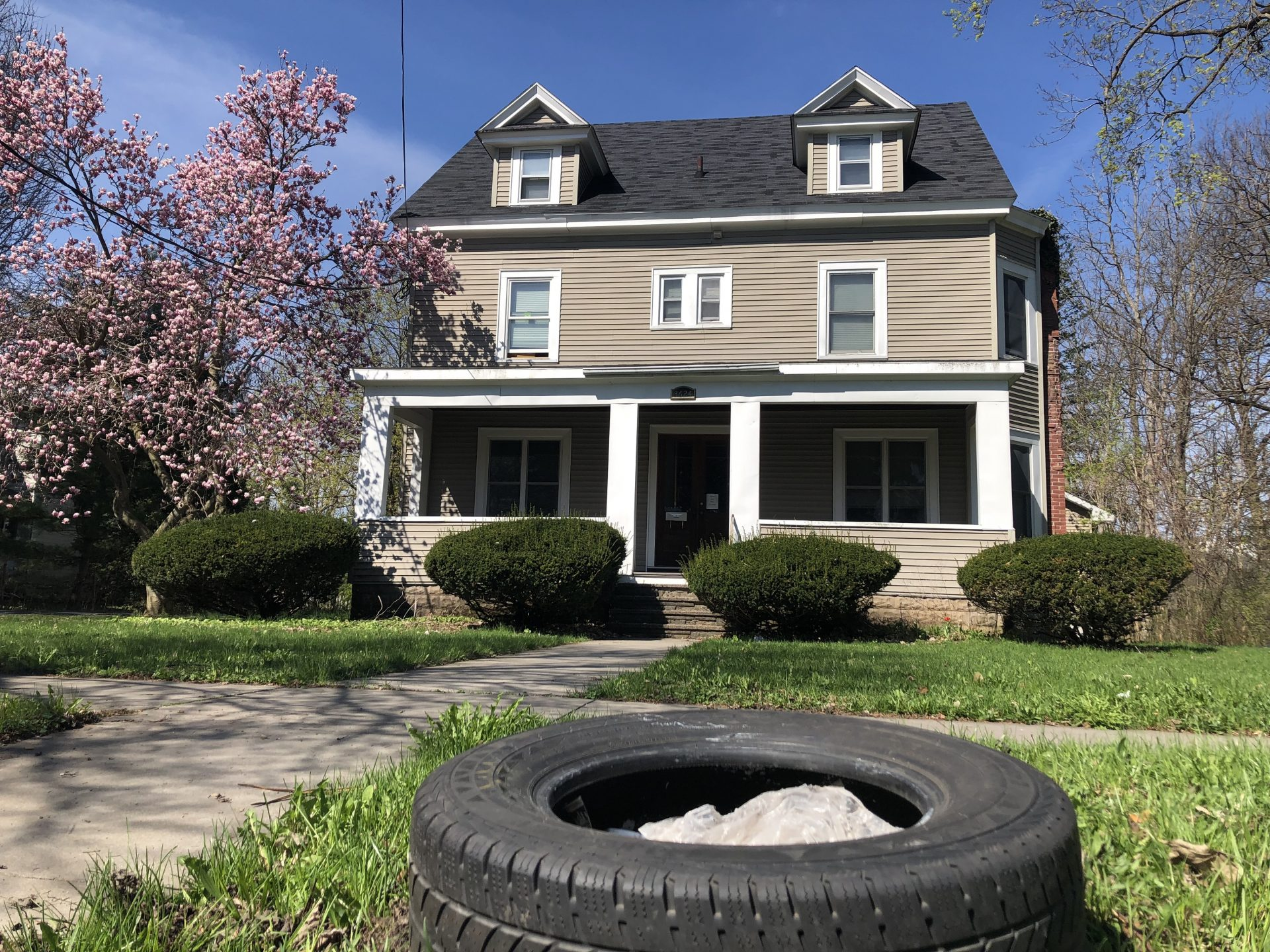 Street view of house with a tire outside on the sidewalk.