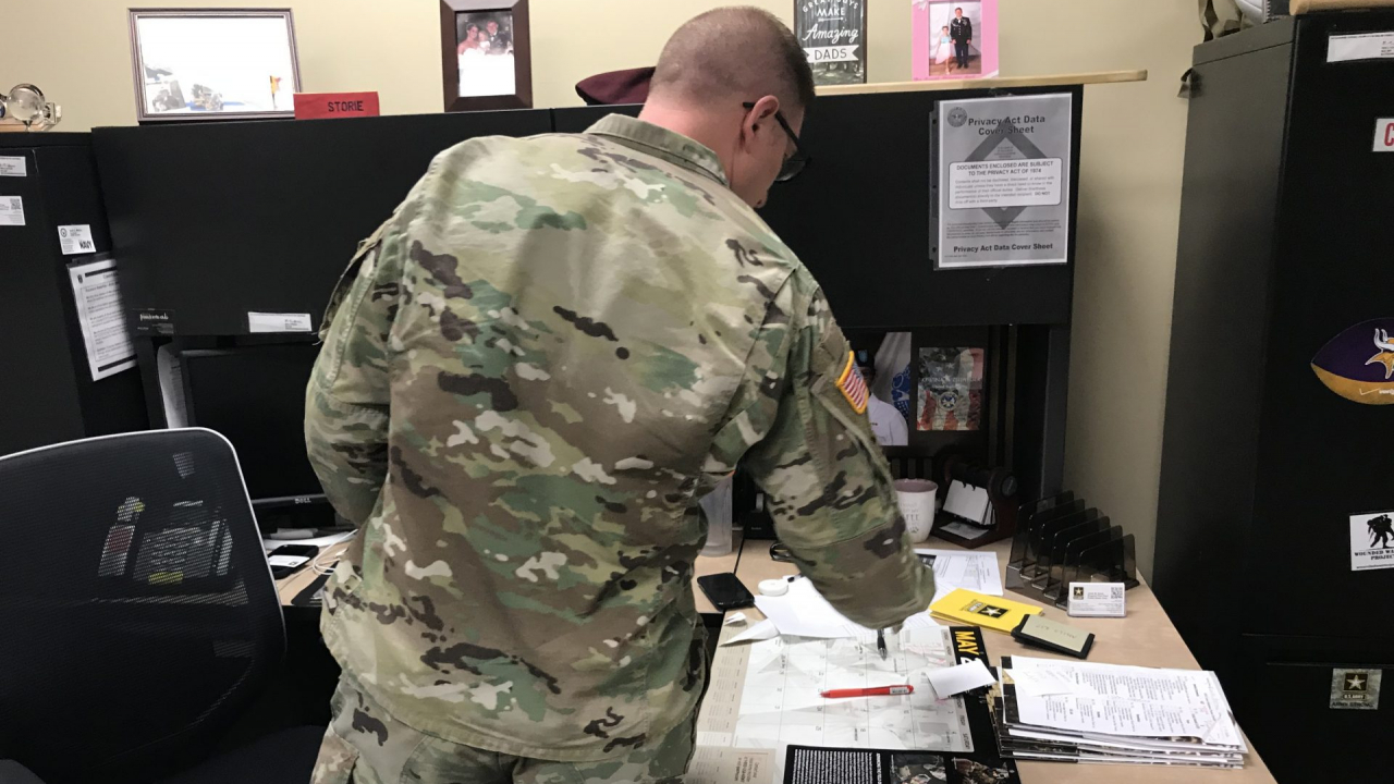 Sergeant First Class Justin Storie shuffles through packets on his desk