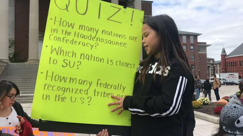 Lila Hill holds a sign quizzing people on trivia for Indigenous People's Day.