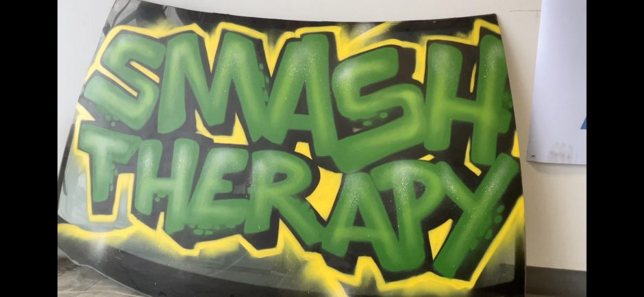 """A car windshield with the words """"smash therapy"""" written across it."""