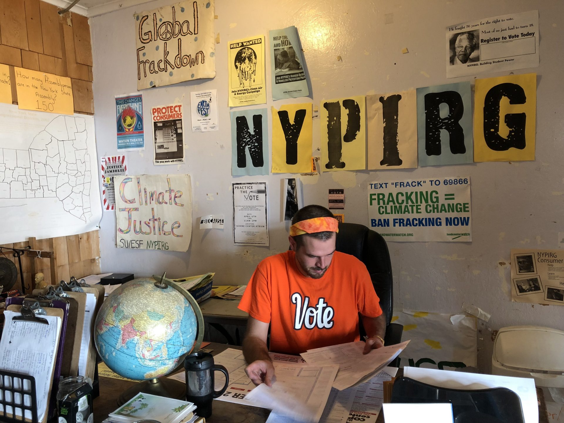 Man sitting at a desk reading voter registration forms