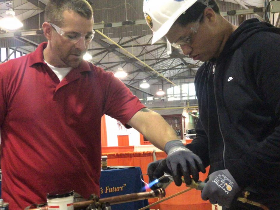Thomas Hayward teaches high school student Jimmie Armstead proper welding technique for plumbing.