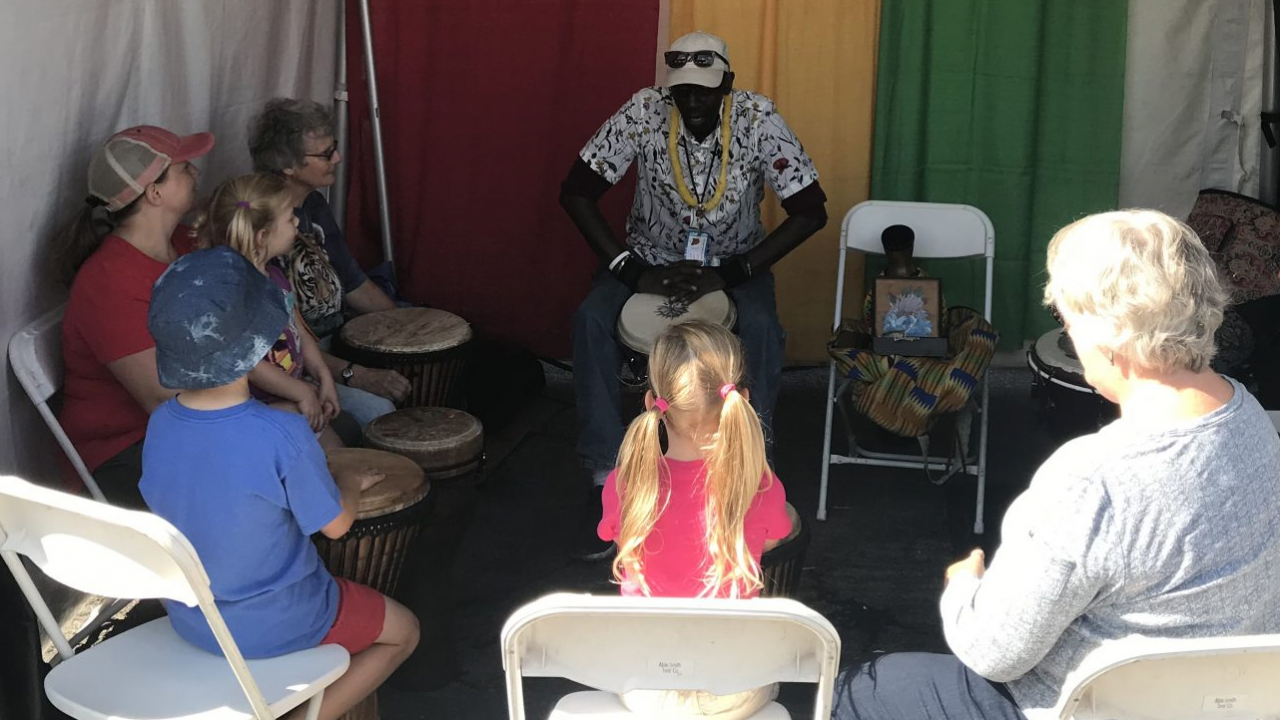 John Heard teaching visitors of the fair ancient African hand drumming and the history of the Djembe Drum.
