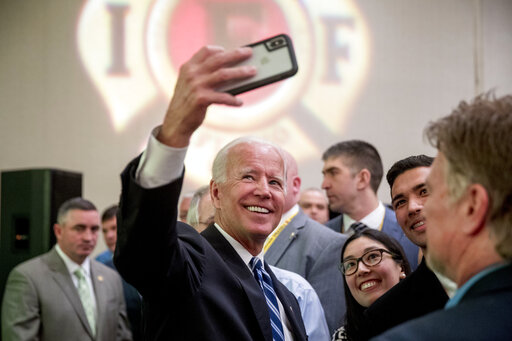 Joe Biden is in the process of taking a selfie with a supporter of his at the International Association of Firefighters on March 12th, 2019.