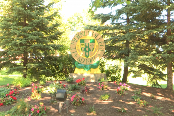Picture of a Le Moyne College sign amongst trees and flowers at one of the entrances to the school.