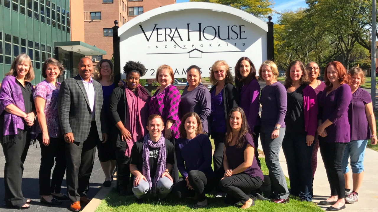 Last year's group photo of Vera House staff, dressed in purple and posing in front of the Vera House sign.