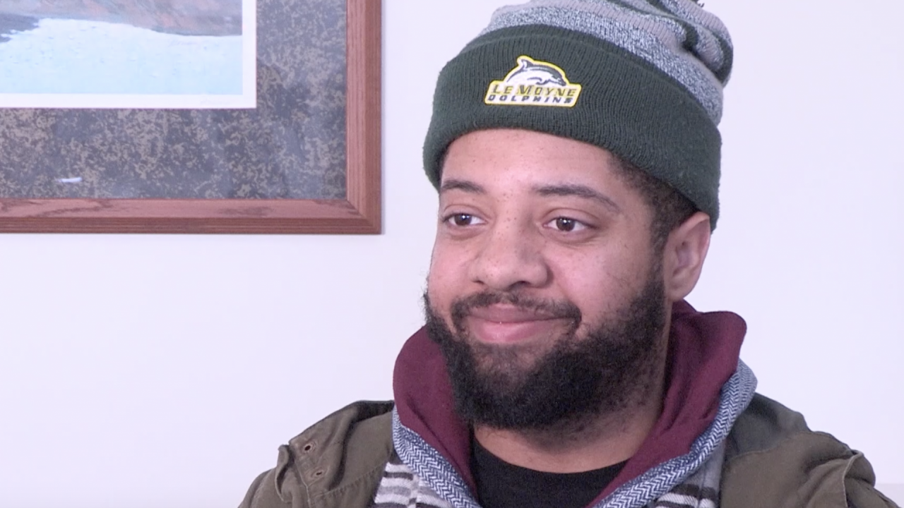 Jeffry Mateo smiles during an interview in the library at Le Moyne college