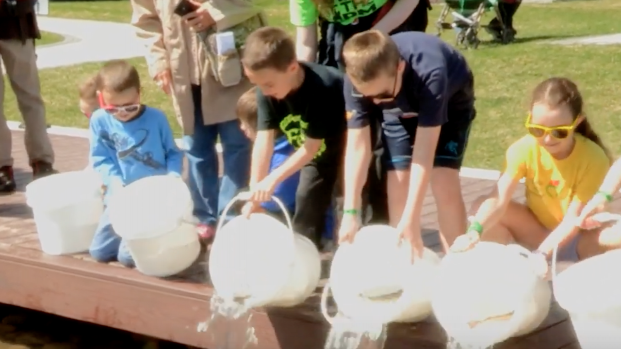 Kids holding buckets filled with fish pour them into Green Lake.