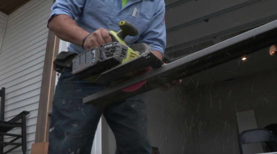 A builder cuts a slab of wood with an electric saw.