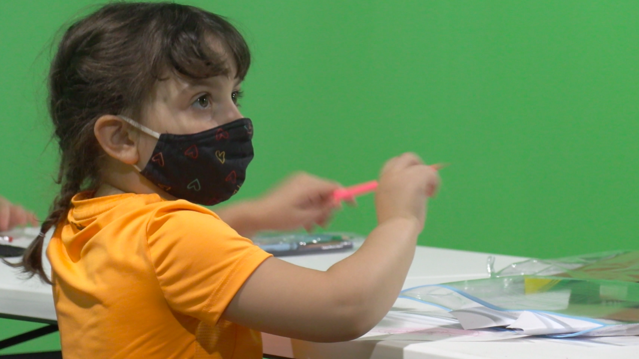 little girl holding a pencil in a mask