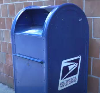 Blue USPS drop box by brick wall