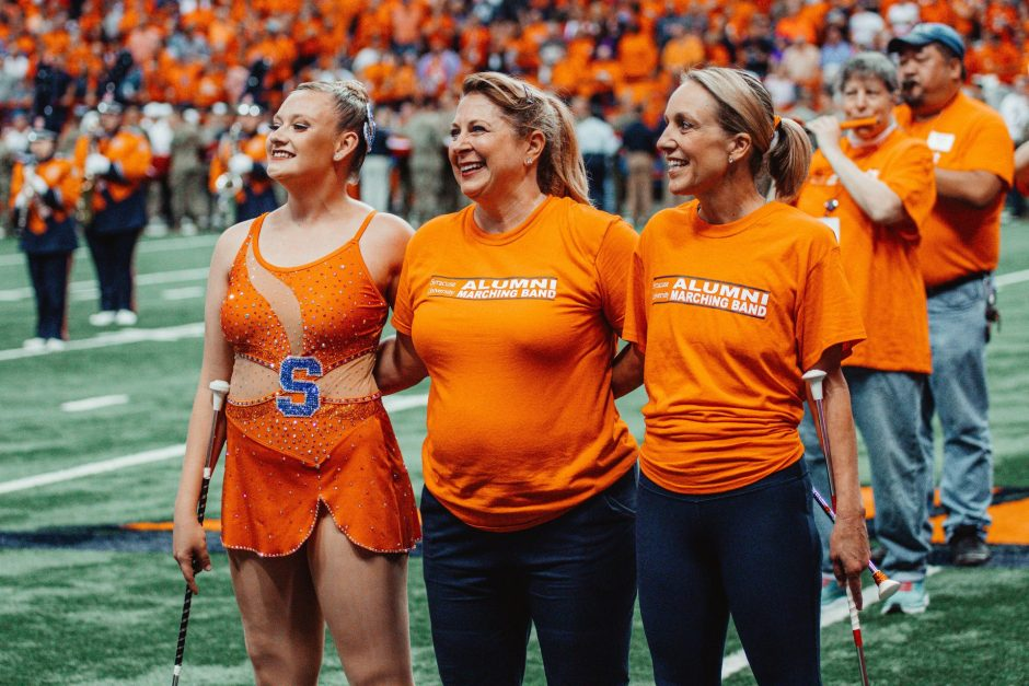 Current Orange Girl Trina Catterson (left) poses on the field at the Homecoming 2019 football game with two twirling alumni.