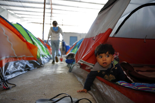 A little toddler peaks out of a tent located in a refugee camp.