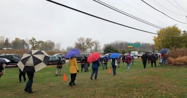 Voters with umbrellas stand outside waiting to cast their ballots on a rainy afternoon in Dewitt.