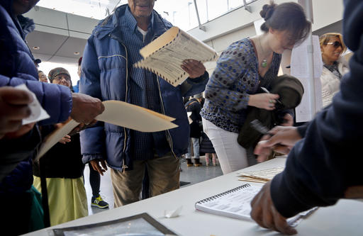 Voters receive their ballots at the Brooklyn Museum polling site, Tuesday Nov. 8, 2016, in Brooklyn, N.Y.