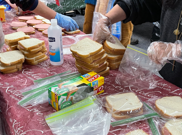We Rise Above The Streets packing sandwiches with volunteers to help feed the homeless and those affected by the pandemic.
