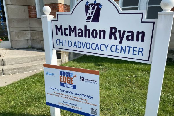 McMahon Ryan Child Advocacy Center sign along with Over the Edge 4 Kids fundraiser yard sign.